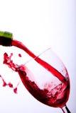 红葡萄酒涌入玻璃 库存图片