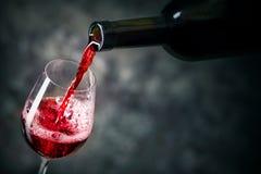 红葡萄酒涌入玻璃 免版税图库摄影