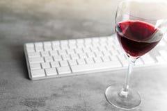 红葡萄酒溢出了在具体桌上的键盘与f 图库摄影
