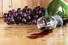 红葡萄酒溢出的和葡萄果子 库存图片