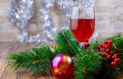 红葡萄酒玻璃和圣诞节球在雪 免版税库存照片