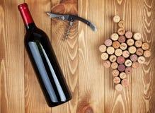 红葡萄酒瓶、拔塞螺旋和葡萄塑造了黄柏 免版税库存照片
