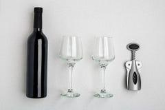 红葡萄酒瓶、玻璃和拔塞螺旋在白色背景 与拷贝空间的顶视图 免版税库存照片