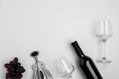 红葡萄酒瓶、玻璃和拔塞螺旋在白色背景 与拷贝空间的顶视图 库存照片