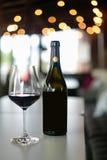 红葡萄酒瓶和酒杯在桌上 库存图片