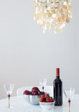 红葡萄酒用在桌上的果子和美丽的枝形吊灯 图库摄影