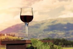 红葡萄酒站立在奥林匹斯山山背景的一张木桌上的一杯在suset发出光线 免版税库存照片