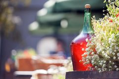 红葡萄酒站立在桶的大葡萄酒酒瓶 老被密封的瓶红葡萄酒 免版税图库摄影