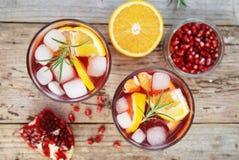 红葡萄酒蔓越桔柑橘石榴桑格里酒 顶视图,土气木背景 免版税库存照片