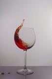 红葡萄酒飞溅在一块圆的玻璃的 免版税库存照片
