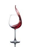 红葡萄酒飞溅在一块玻璃的在白色背景 免版税库存照片