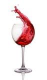 红葡萄酒飞溅在玻璃的 免版税库存图片