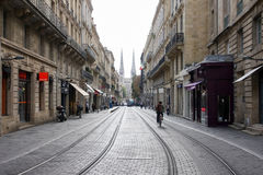 红葡萄酒,法国, 2011年10月18日:有电车轨道路轨的重要卡莱斯街道和圣徒安德烈教会在背景中 免版税图库摄影