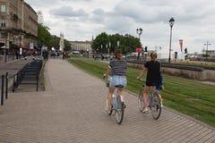 红葡萄酒,阿基旃/法国- 06 10 2018年:两个女孩做着循环在红葡萄酒码头的自行车  免版税库存照片