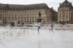红葡萄酒,阿基旃/法国- 06 10 2018年:跳舞和飞溅水镜子到位de la bourse的女孩在红葡萄酒, 库存图片
