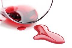 红葡萄酒从玻璃溢出 库存照片