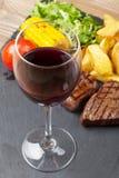 红葡萄酒玻璃和牛排用烤土豆,玉米,沙拉 库存照片