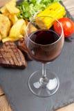 红葡萄酒玻璃和牛排用烤土豆,玉米,沙拉 库存图片