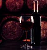 红葡萄酒玻璃近的瓶在木桌上和在老葡萄酒库背景中 库存图片