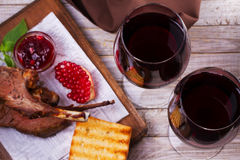 红葡萄酒玻璃 放在架子上的羊羔用石榴调味汁和绿色 库存图片