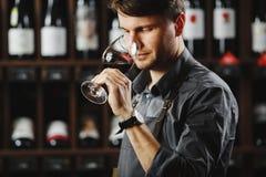 红葡萄酒Bokal在背景,赞赏饮料的男性斟酒服务员的 库存照片