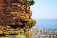 红褐色的岩石特写镜头的一个大部分反对蓝色海的 库存照片