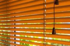 红褐色的软百叶帘的片段在窗口和blurre的 免版税图库摄影