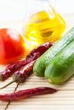 红辣椒、黄瓜、蕃茄和瓶上油 免版税图库摄影