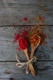 红辣椒和番红花在木匙子在土气桌上,五颜六色的印地安香料 免版税库存图片