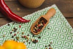 红辣椒和色的胡椒在厨房餐巾 免版税库存照片