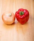 红辣椒和黄色葱在木表上 免版税库存照片