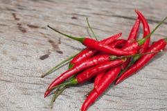 红辣椒,新鲜的多五谷投入了一个老木桌好漂亮的东西或人 免版税库存图片