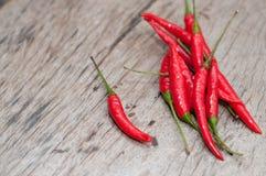 红辣椒,新鲜的多五谷投入了一个老木桌好漂亮的东西或人 图库摄影