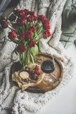 红酒、快餐和红色郁金香在被编织的毯子 库存图片