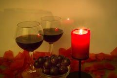红酒酒杯,葡萄,燃烧的蜡烛,和上升了在桌上的叶子 免版税图库摄影