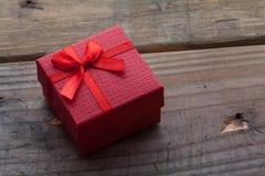 红颜色有弓的礼物盒在木背景 免版税库存图片