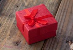 红颜色有弓的礼物盒在木背景 库存照片