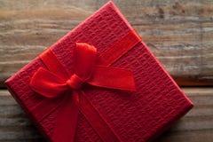 红颜色有弓的礼物盒在木背景 免版税图库摄影