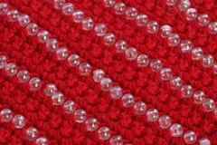红颜色被编织的织品与小珠装饰的  免版税库存照片