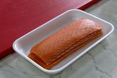 红鲑鱼内圆角在一个白色长方形杯子钓鱼在切板旁边 烹调的成份寿司和卷的 日语 库存图片