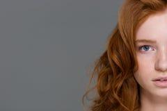 红头发人卷曲妇女的半面孔有美丽的长的头发的 免版税库存图片