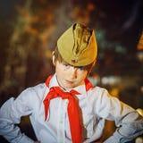 红头发人可爱的男孩穿戴了象与红色领带的苏联先驱 免版税库存图片