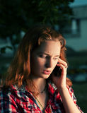 红头发人女孩叫由手机 免版税库存照片