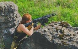 红头发人女孩战士准备从后面盖子开火 图库摄影