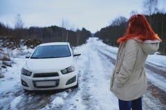 年轻红头发人女孩看她残破的汽车 库存照片
