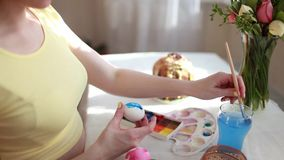 红头发人女孩绘与刷子的复活节彩蛋 在桌复活节蛋糕,鸡蛋,甜点,花花束  影视素材
