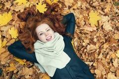 红头发人女孩说谎在叶子的和闪光在城市停放,秋季 图库摄影