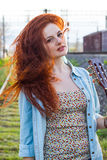 年轻红头发人女孩画象有吉他的 库存照片