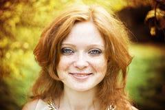 红头发人女孩画象有蓝眼睛的在自然 免版税图库摄影