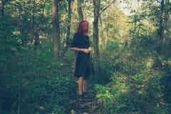 年轻红头发人妇女在森林 免版税库存图片